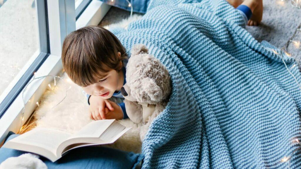 boy under blanket with teddy